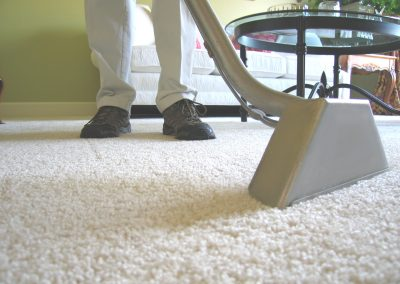 Man cleaning white carpet with industrial vacuum